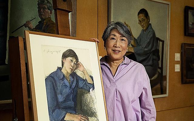 父・永井潔さんの描いた肖像画と。奥右は祖母・志津さんの肖像画、左は潔さんの自画像=慎芝賢撮影
