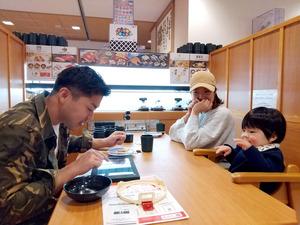 高い背もたれのボックス席で食事を楽しむ親子=くら寿司吉祥寺駅前店