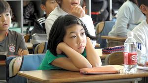 国語「ちいちゃんのかげおくり」で、先生が読む物語に聴き入る子どもたち。和光小学校では、教科書を使わずに授業が進む=映画「あこがれの空の下」から