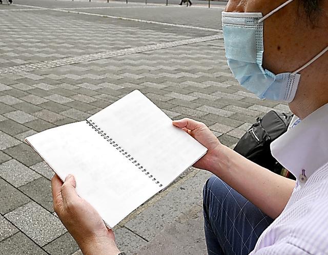 男性が発熱するなどした病状をつづったノートを手にする長男(画像の一部を加工しています)