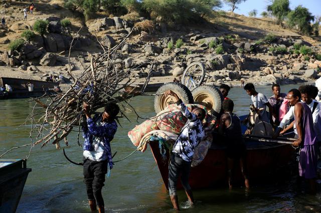 スーダン東部カッサラ州にある国境付近で11月22日、ボートで川を渡り避難してきたエチオピアの人々が荷物を下ろしていた=ロイター