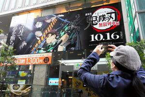「劇場版『鬼滅の刃』無限列車編」の上映初日の映画館前では、写真を撮る人の姿も見られた=2020年10月16日午前7時4分、東京都新宿区、瀬戸口翼撮影