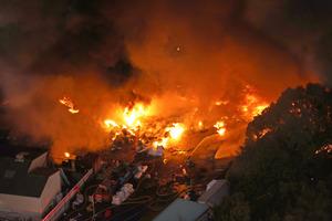黒煙をあげて燃える建物の消火活動が続いていた=2020年12月5日午後5時5分、大阪府和泉市、朝日新聞社ヘリから、矢木隆晴撮影
