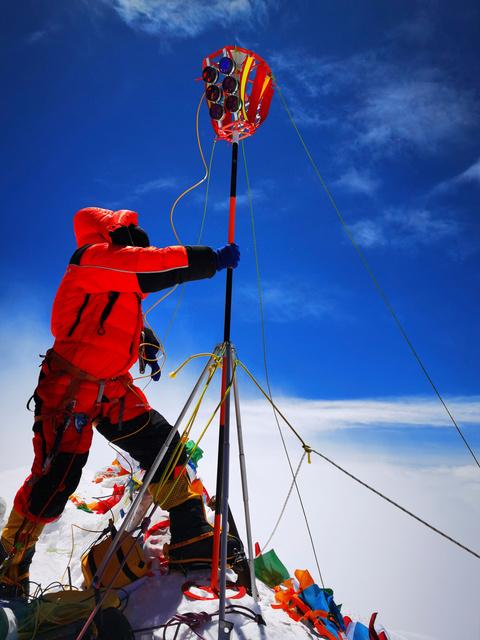 5月27日、エベレスト(チョモランマ)の頂上に測量機器を設置する中国の測量隊。新華社通信が配信した=AP