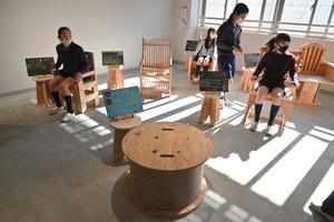 新渡戸文化学園のVIVISTOPに展示された12脚のイス。座り心地を確かめる児童ら=東京都中野区