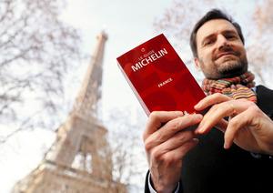 パリで18日、ミシュランガイド2021年版を手にポーズをとるガイドの総責任者グウェンダル・プレネックさん=ロイター