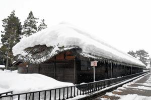 手前の屋根が陥没した足軽長屋。17日からの大雪で、屋根には分厚い積雪が残っていた=2021年1月19日午後2時35分、新潟県新発田市