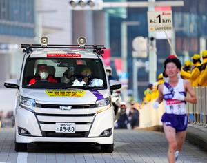 10区、石川拓慎(右)に車から声をかける駒大・大八木弘明監督(中央)=代表撮影