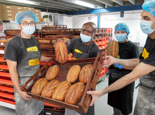 焼きたてのライ麦パン「サワードー」を見せるジャン・ロバートさん(左から2人目)、マドゥさん(同3人目)ら=2月3日、シドニー、小暮哲夫撮影