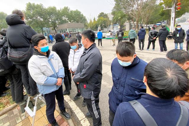 中国・武漢で2月2日、世界保健機関(WHO)調査団を取材しようと集まった報道陣の前に壁をつくる私服の男たち=高田正幸撮影