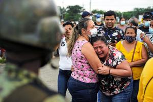 エクアドルのグアヤキルで23日、暴動が起きた刑務所の外で泣く女性=ロイター