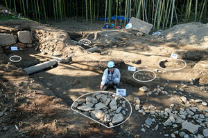 永原御殿跡で見つかった「南之御門」の柱を据えた跡(白い円)=2021年2月22日午後2時56分、滋賀県野洲市永原
