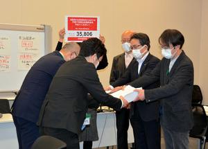 厚生労働省に扶養照会の見直しを求める署名を提出する「つくろい東京ファンド」と生活保護問題対策全国会議=2021年2月8日、東京都千代田区永田町2丁目