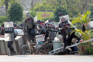 ミャンマーのマンダレーで2月28日、国軍のクーデターに抗議するデモ参加者が設置した障害物を乗り越える警官隊=AP