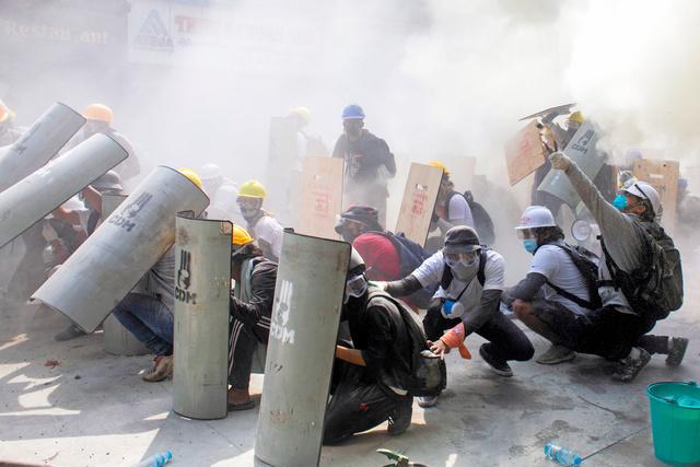ヤンゴンで2月28日、国軍によるクーデターに抗議する中、機動隊と衝突して、身を潜めるデモ参加者たち=ロイター