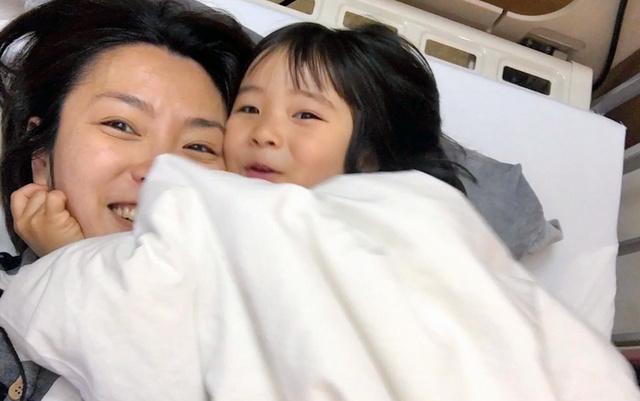 入院中、布団に潜り込んできた娘と=尾崎さん提供