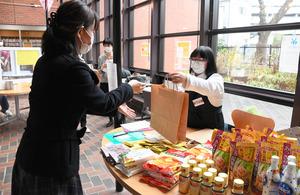 食料を受け取る女性(左)=2021年3月7日午前11時42分、横浜市南区南太田1丁目、岩本修弥撮影
