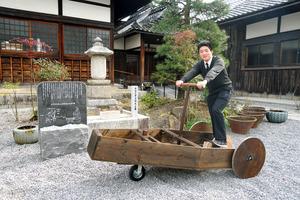 「陸舟奔車」製作の中心になった村西晃徳さん。左は平石久平次の墓=2021年2月12日午後2時12分、滋賀県彦根市中央町の長松院