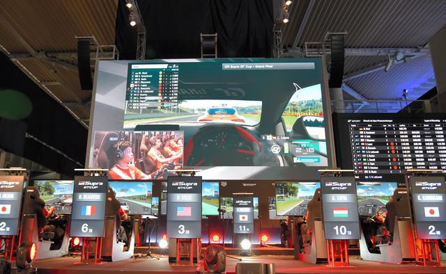 巨大スクリーンの前で競うeモータースポーツの大会参加者。コロナ前は一つの会場に集まってプレーしていた=2019年10月26日、東京・お台場、中川仁樹撮影