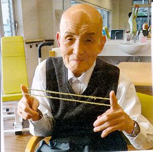 介護施設であやとりをする遠藤節子さんの父守男さん。「外面が良いのでどこでもニコニコ。私には見せない表情です」=遠藤さん提供