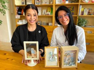 テレサ・クリアさん(右)の描いた作品を手にする「アンサーノックス」の渡辺郁さん=2021年4月14日午後2時32分、甲府市丸の内2丁目、平山亜理撮影