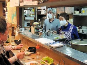 常連客と談笑する須磨子さん(右端)=2021年4月20日午後6時1分、東京都千代田區丸の內3丁目、砂押博雄撮影