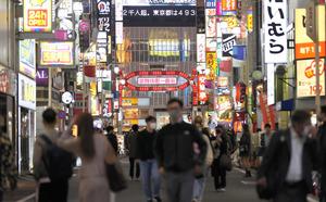 多くの飲食店が立ち並ぶ新宿・歌舞伎町。電光掲示板では、新型コロナウイルスの国内感染者が初の2千人超えのニュースを報じていた=2020年11月18日午後7時39分、東京都新宿区、藤原伸雄撮影
