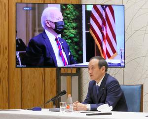 気候変動サミットで日本の温暖化対策について話す菅義偉首相。画面ごしには米バイデン大統領がいる=内閣広報室提供