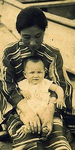 母のひざに抱かれる、赤ん坊のころの角野さん=本人提供