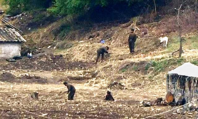 北朝鮮の農村で作業する、軍人とみられる人たち=2021年4月、中国・遼寧省から、平井良和撮影
