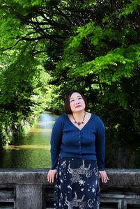 遊郭のあった五条楽園のそばを流れる高瀬川を背に撮影に応じる作家の花房観音さん=京都市下京区、小杉豊和撮影