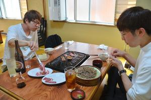 「マトンが食べたくなって」。隣接する浜松市天竜区からやってきたという2人が肉をほおばっていた=6日、長野県飯田市