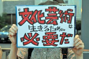 首相官邸前でのサイレントスタンディング。「文化芸術は生きるために必要だ」と手描きのメッセージを掲げる女性=6日夕、東京都千代田区