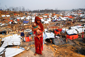 バングラデシュ南東部コックスバザールの難民キャンプでは3月、大規模な火災が発生し、多くの家屋が焼失した。被害を受けたキャンプで子どもを抱く女性=ロイター