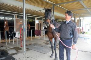 引退後の競走馬を受け入れ、学生の訓練に使う馬事学院。手綱を持つのが野口佳槻代表=2021年4月9日午後3時56分、八街市の馬事学院