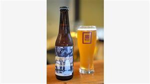 一関市の直営店で提供されているノンアルコールビール「禁酒時代のヒール」(右)と試作ラベルが巻かれた瓶=岩手県一関市、三浦英之撮影
