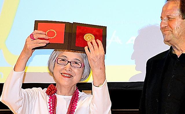 国際アンデルセン賞の授賞式で、贈られたメダルを掲げる角野さん=2018年、アテネ