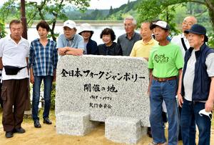 除幕された記念碑。当時の実行委員らが記念撮影をしていた=2021年6月12日、岐阜県中津川市上野、戸村登撮影