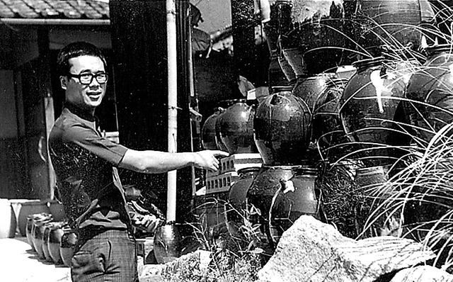 堀越焼の窯場で古い焼酎つぼを前に=1975年、山口県防府市、本人提供
