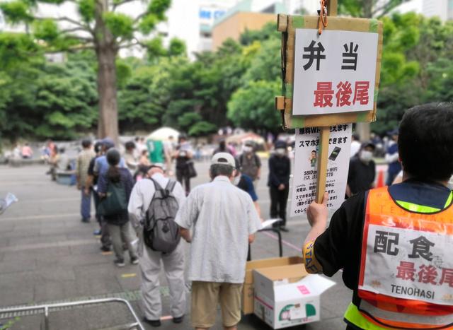 NPO法人TENOHASIの炊き出し。この日はコロナワクチン接種に関するチラシも配られた。コロナ禍のなかで集まる人数は急増していて、380人が列をつくった=6月12日、東京都豊島区