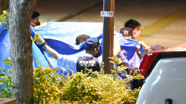 立てこもり現場から、容疑者とみられる人物をブルーシートで囲みながら出てきた捜査員ら=2021年6月18日午後10時47分、さいたま市大宮区、加藤諒撮影