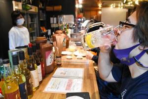 燻製料理の盛り合わせをノンアルコールのレモンサワーで流し込む客。「燻製の味とビールはひも付いている。飲みたい」とぼやいた=2021年6月15日午後7時43分、京都市中京区、高井里佳子撮影