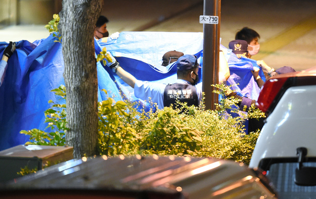 立てこもり現場から、容疑者と見られる人物をブルーシートで囲みながら出てきた捜査員ら=2021年6月18日午後10時47分、さいたま市大宮区、加藤諒撮影