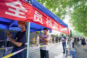 7月29日、中国・江蘇省南京市のPCR検査場の列に並ぶ人たち=新華社。同市では3巡目となる全住民のPCR検査が実施されていた