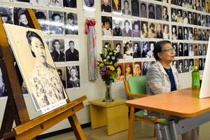 長岡空襲の体験を話す池田ミヤ子さん。左の写真は空襲で亡くなった長姉の寿美子さん=7月11日、長岡市城内町2丁目の長岡戦災資料館