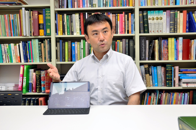 アフガニスタンを訪れたときの様子をタブレットを使って説明する東京外国語大学講師の登利谷正人さん=東京都府中市、半田尚子撮影