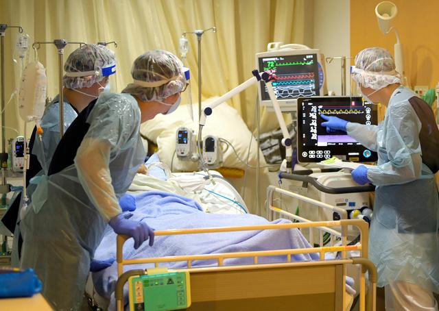 人工呼吸器をつけた新型コロナの重症患者を診る医師ら=2021年9月、東京都文京区の都立駒込病院