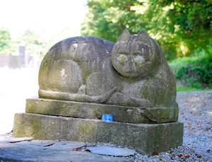 少し悲しげな表情の「猫神様」の石像。足元には缶詰が供えられている=2021年8月4日、岩手県一関市、三浦英之撮影