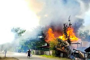 ミャンマー中部マグウェーで9月10日、国軍と抵抗する人たちとの間で戦いが続くなか、家屋から上がる火を消そうとする人々。写真は匿名の人物から提供された=AFP時事