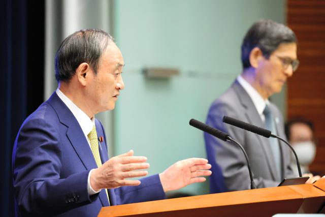 緊急事態宣言とまん延防止等重点措置の全面解除を決定し、質問に答える菅義偉首相(左)=2021年9月28日午後7時22分、首相官邸、上田幸一撮影